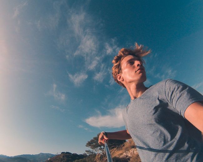 Low Angle View Of Young Man Standing Against Blue Sky