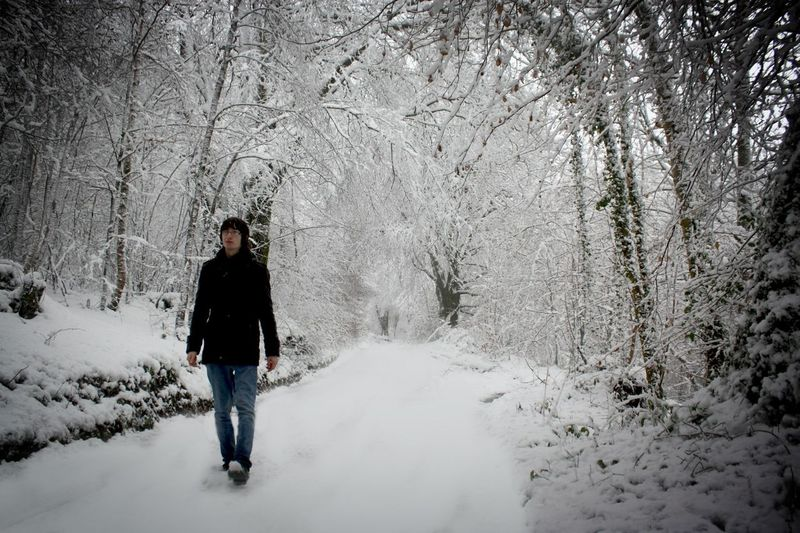 Young man walking on snowcapped road amidst frozen bare trees