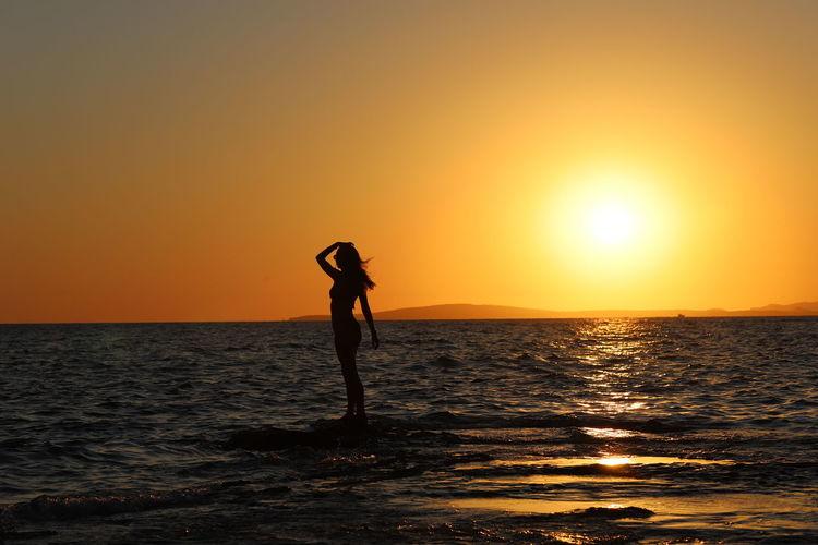 Silhouette woman standing on sea against orange sky