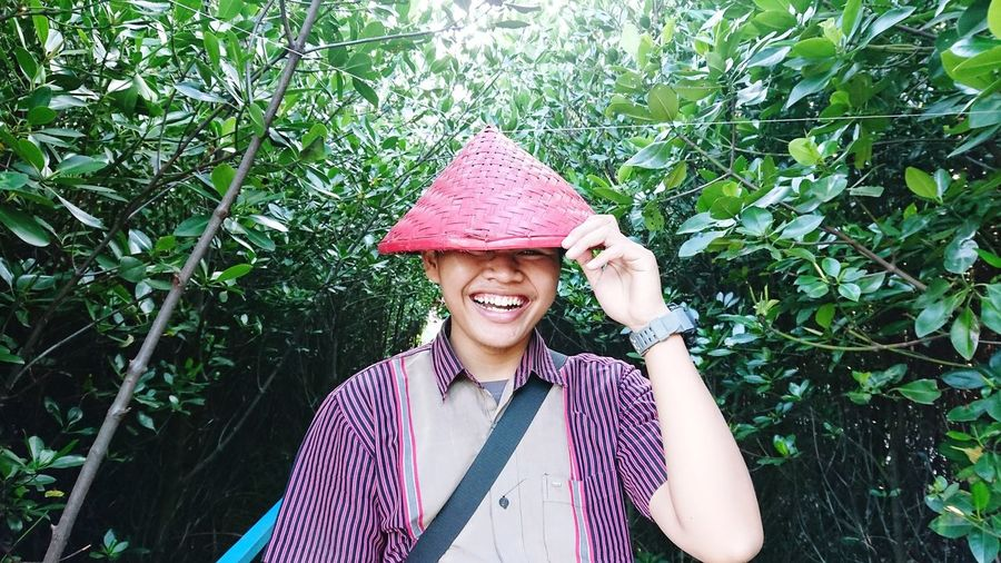 Smiling young woman wearing hat standing against plants