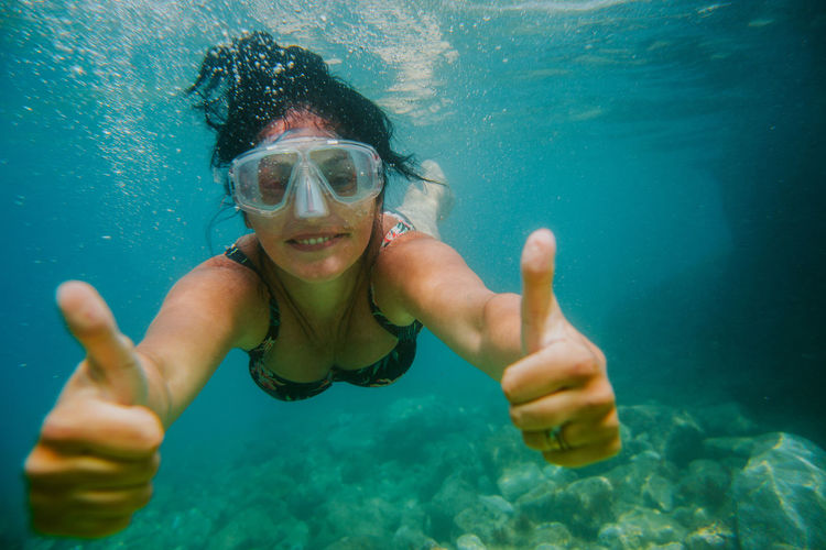 Portrait of woman swimming while gesturing thumbs up sign in sea