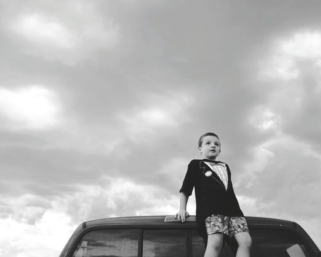 Low Angle View Of Boy Relaxing On Car Against Cloudy Sky