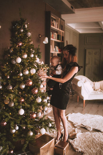 Full length of mother carrying son while standing by christmas tree