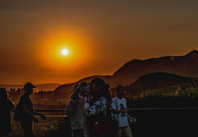 People standing on mountain against orange sky