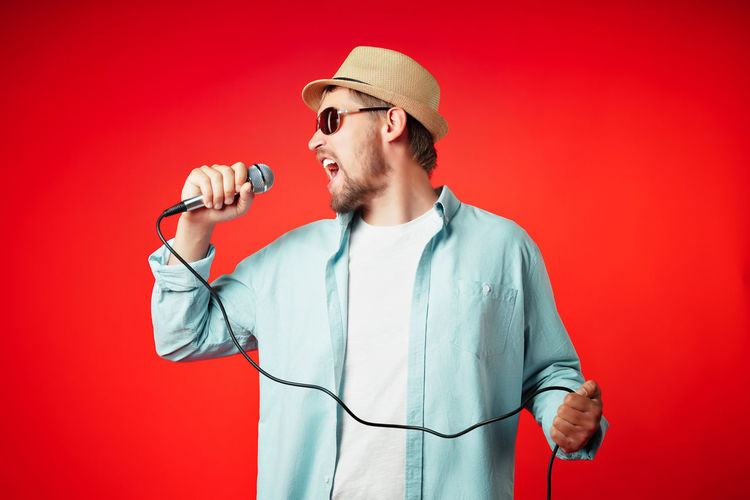Midsection of man holding hat against red background