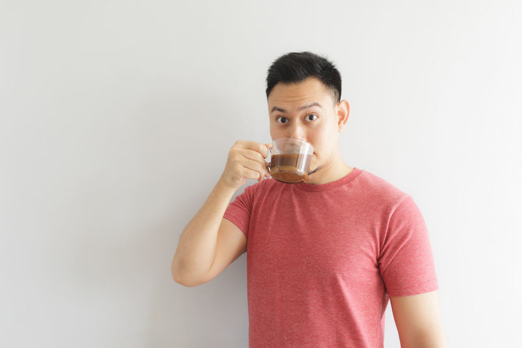 Midsection of man drinking glass against white background