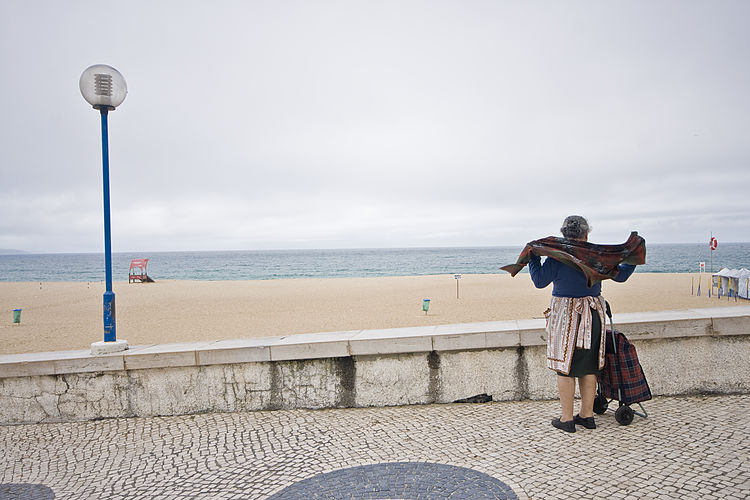 """"""" I'm heading to the market, the earlier the better. But I always stop here before I go to look at the sea"""" Situated in the Portuguese Silver Coast, Nazare is a small fishing village in Portugal. Long an inspiration for many photographers and cinematographers, including a young Stanley Kubrik, Nazare has a very unique local culture intrinsically connected with the oceans with a long and rich sea tradition, embedded in local folklore. The Woman of Nazare ( Nazarena) for example, is the column that holds the community together and has been immortalised in monuments locally. When the men were at sea for months on end, the Woman of Nazare took care of family, business (usually selling fish and other sea produce) and everything else on land. This is even reflected in traditional attire. The """"7 skirts"""" (Sete Saias) for example, were in fact mostly work or utility aprons and shawls, exquisitely decorated and usually made by hand. When the men were returning from the sea with the catch, usually at night, the women would then be waiting on the beach and the aprons would turn to shawls becoming protective layers that they would wrap themselves with gradually as the cold set it. The sea was both the source of sustenance as well as of a lot of sorrow. Many women had lost husbands, sons and brothers at sea and many would trade in the colourful attire for black in mourning, a trait that it is still observed today. Some women continued their mourning to the end of their lives. Over the years, the fishing industry started to decline as both overfishing and the lack of interest of the younger generations in it, impacted local economy.. Nazare then turned to tourism as the main source of business, particularly in the Summer, season in which it is common for the locals to rent property to tourists over the summer (although nowadays, tourism is all year round, as Nazare became one of the best surfing destinations in the world, brought to world attention by surfer Garrett McNamara for i"""