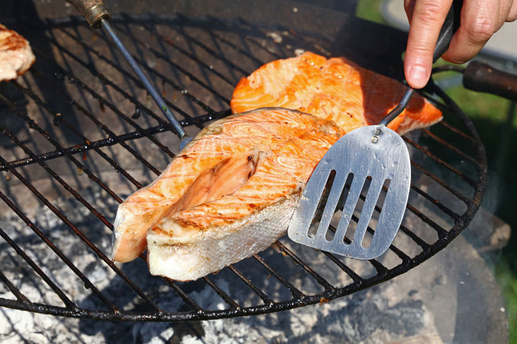 Cropped hand of person cooking salmon steaks on barbecue grill