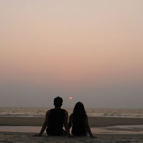 Rear view of couple at beach against sky during sunset