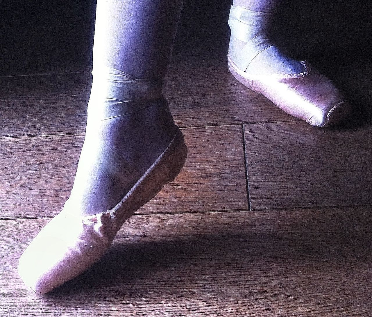 low section, human leg, ballet, indoors, flooring, ballet dancer, hardwood floor, real people, practicing, balance, one person, flexibility, skill, human body part, close-up, ballet studio, day, people