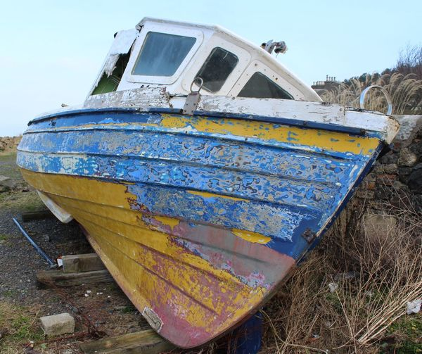 Close-up of abandoned boat on shore