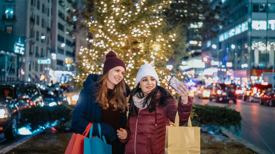 Happy friends on illuminated city street