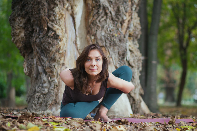 Portrait of beautiful young woman lying on tree trunk in forest