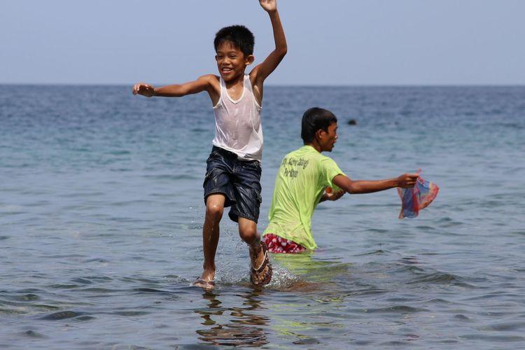 Siblings playing in sea against sky