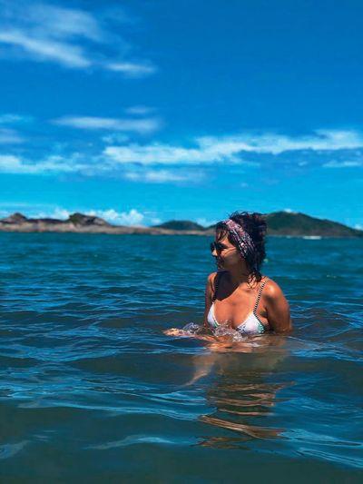 Smiling bikini woman swimming in sea against blue sky