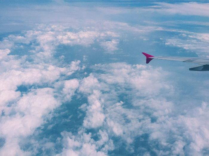 Low angle view of airplane flying over clouds
