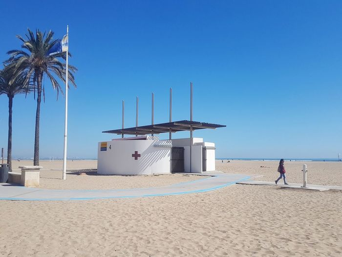 Minimalism Minimalist Architecture Beach Architecture_collection Urban Geometry Streetphotography Street Streetphoto_color Communication Clear Sky Sea Water Beach Blue Sand Palm Tree Lifeguard  Standing Full Length Lifeguard Hut Sand Dune Wind Power My Best Photo