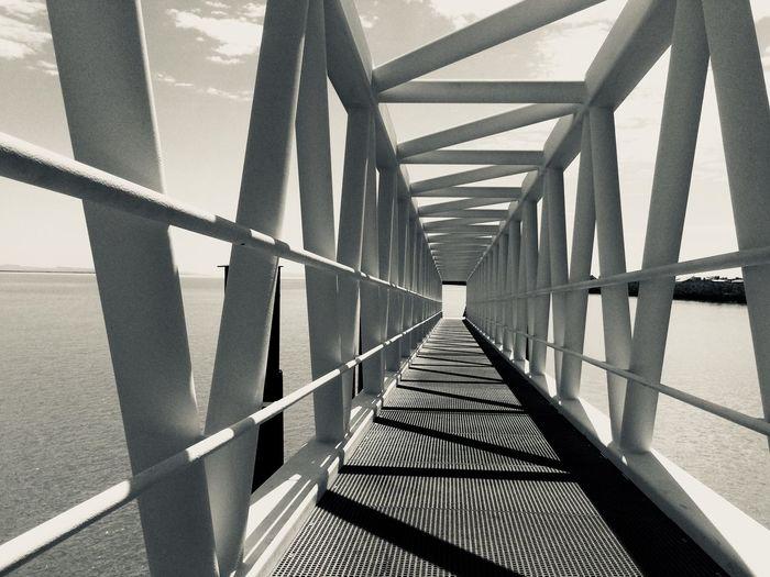 Metallic footbridge over sea during sunny day