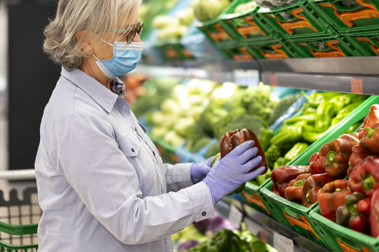 Side view of senior woman wearing mask shopping at store