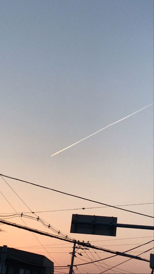 Low angle view of vapor trails against sky