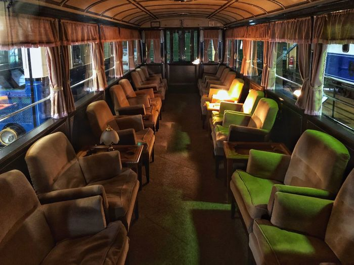 Interior of an old train passenger car. Old Carriage Train Seat Mode Of Transportation Vehicle Interior Vehicle Seat Transportation Indoors  Chair Empty Absence No People Illuminated Travel Public Transportation In A Row Table Luxury Window