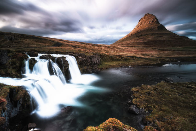 Kirkjufellsfoss and Kirkjufell Mountain Landscape Waterfall Cloud - Sky Water Scenics Lake No People Outdoors Nature Travel Destinations Mountain Sky Beauty In Nature Day Lost In The Landscape Long Exposure Taking Photos Landscape_Collection Iceland Memories