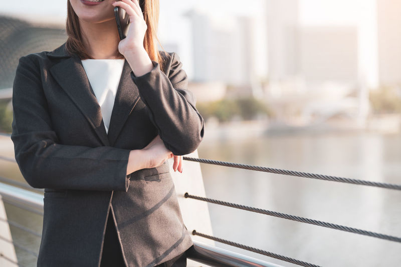 Midsection of businesswoman talking over smart phone while standing by railing