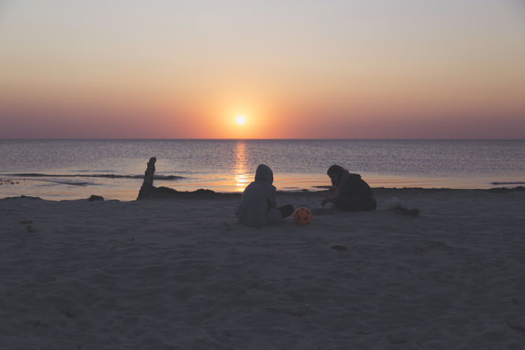 People sitting on beach during sunset