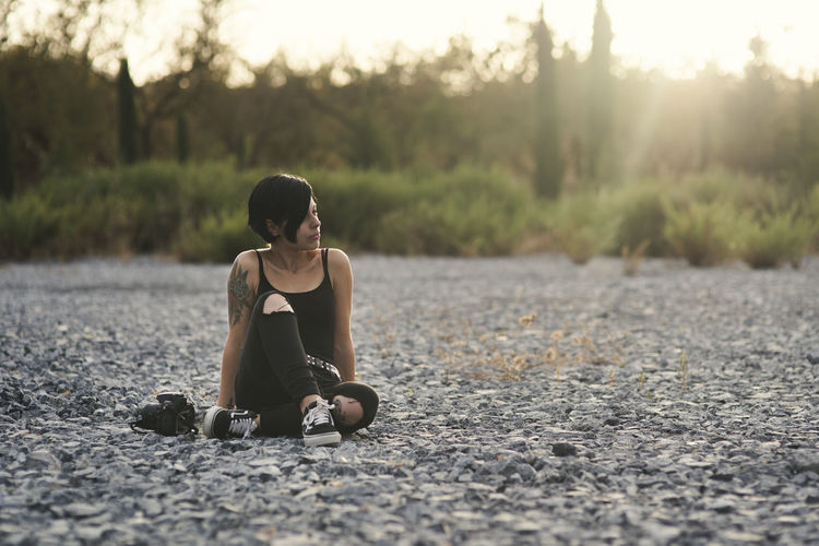 Beautiful young photographer woman wearing black clothes and short haircut sitting on the stone floor brunette girl thinking relaxed in the countryside. Casual Clothing Day Full Length Hairstyle Land Leisure Activity Lifestyles Nature One Person Outdoors Plant Real People Road Selective Focus Sitting Street Sunlight Teenager Transportation Tree Young Adult