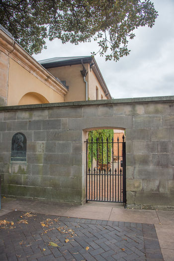 Sydney,NSW,Australia-November 19,2016: Hyde Parks Barracks Museum boundary wall with gate in Sydney, Australia. Architecture Australia Boundary Entrance Gate Tourist Attraction  UNESCO World Heritage Site Wall World Heritage Architectural Detail Architectural Feature Barracks Brick Built Structure Convict Gateway Historic Hyde Park Barracks Masonry Metal Museum Queen's Square Site Sydney Tourism