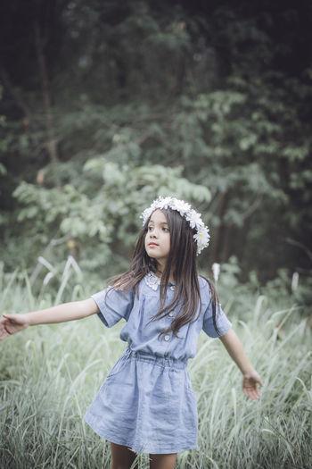 Cute girl wearing flowers standing on grassy field