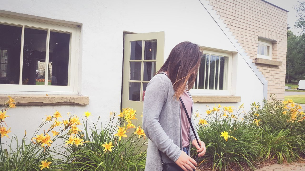 building exterior, architecture, house, built structure, one person, real people, mid adult women, mid adult, day, outdoors, growth, lifestyles, standing, women, young women, smiling, flower, young adult, people
