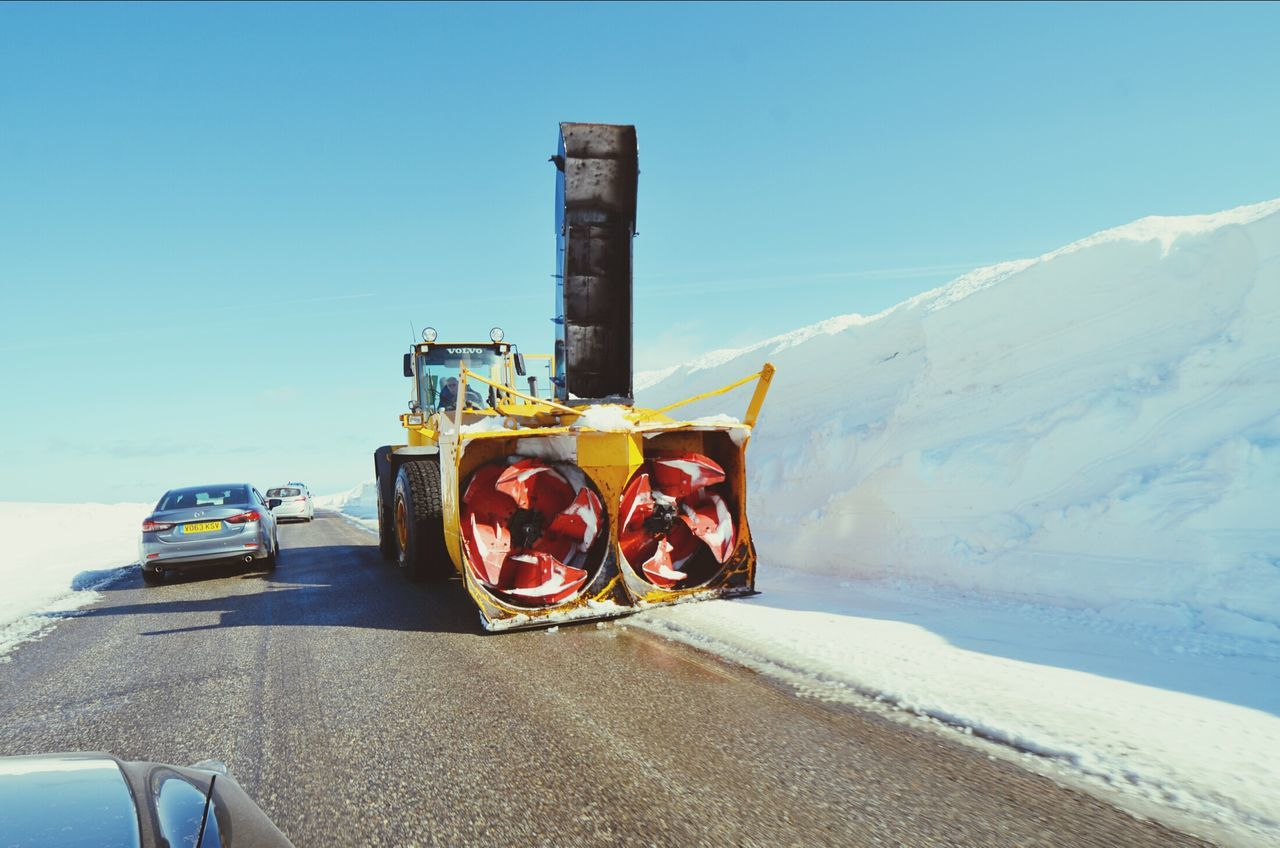Snowblower on road against clear blue sky