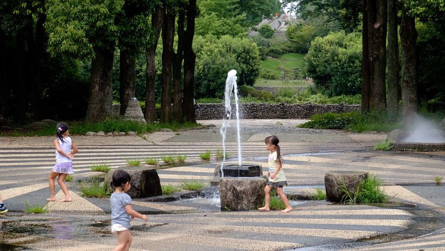 Girls playing by fountain at showa memorial park