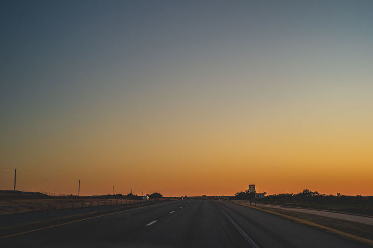Road against clear sky during sunset