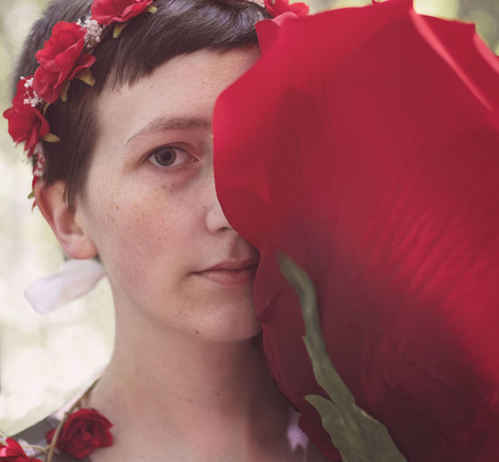 Close-up portrait of woman with red flower