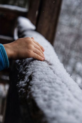 Cropped hand of woman touching snowy railing