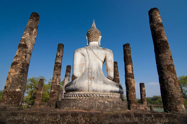 Low Angle View Of Buddha Statue At Ancient Wat Mahathat Against Sky