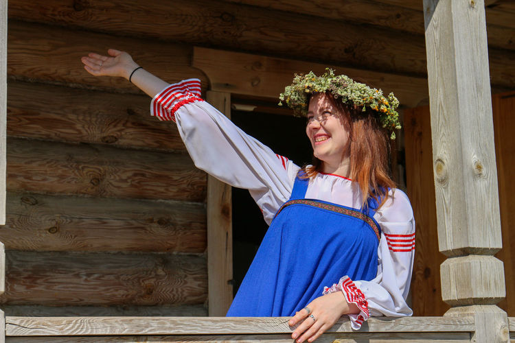 Happy young woman with arm raised standing by railing of house