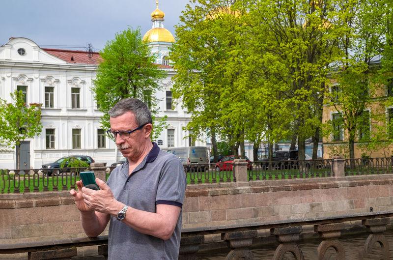 Full length of man using mobile phone against trees