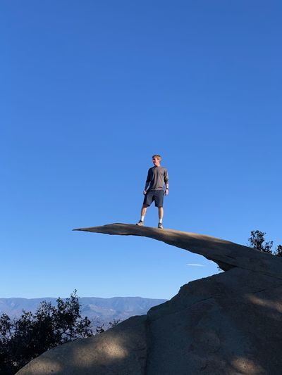Low angle view of man standing on mountain against clear blue sky
