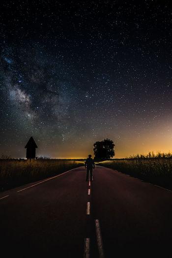 A man looking at the milky way in a dark way