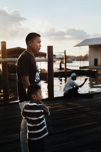 Father with son standing in water against sky