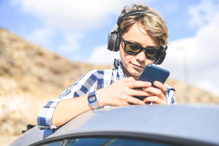 Boy using smart phone against sky