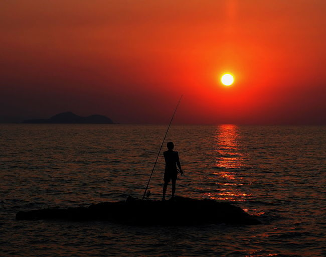 Silhouette Man Fishing In Sea Against Sky During Sunset