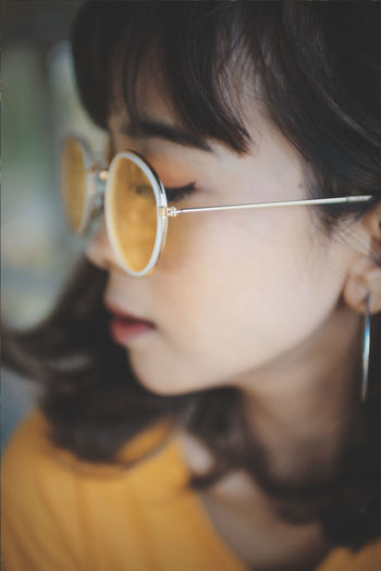 Close-up of young woman wearing sunglasses at home