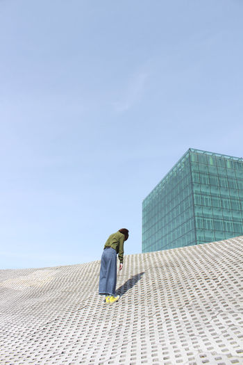 Sky One Person Architecture Real People Built Structure Building Exterior Rear View Day Full Length Clear Sky Nature Lifestyles Blue Leisure Activity Casual Clothing Adult City Building Copy Space Office Building Exterior Outdoors Skyscraper Girl Green Color Shadow Glass
