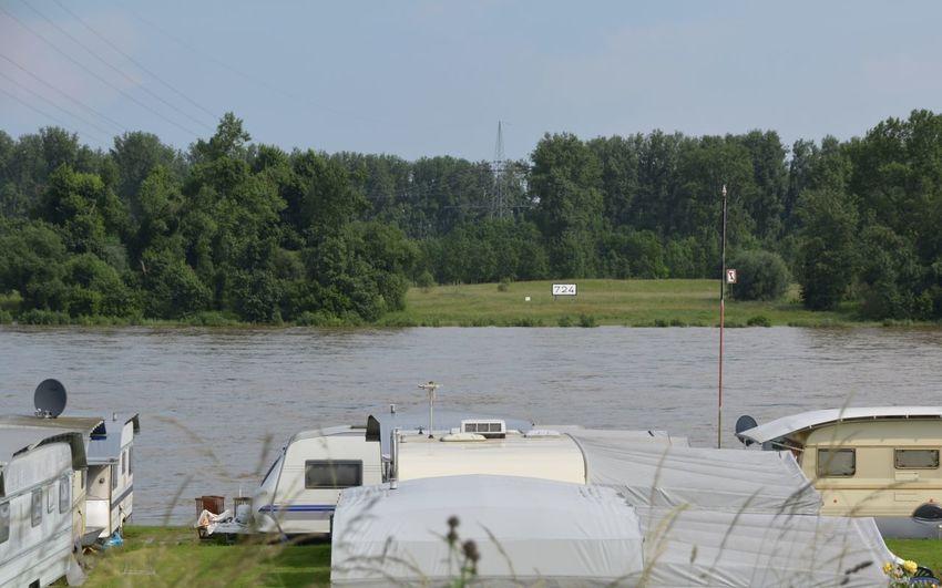 Camping Vans By River Against Sky