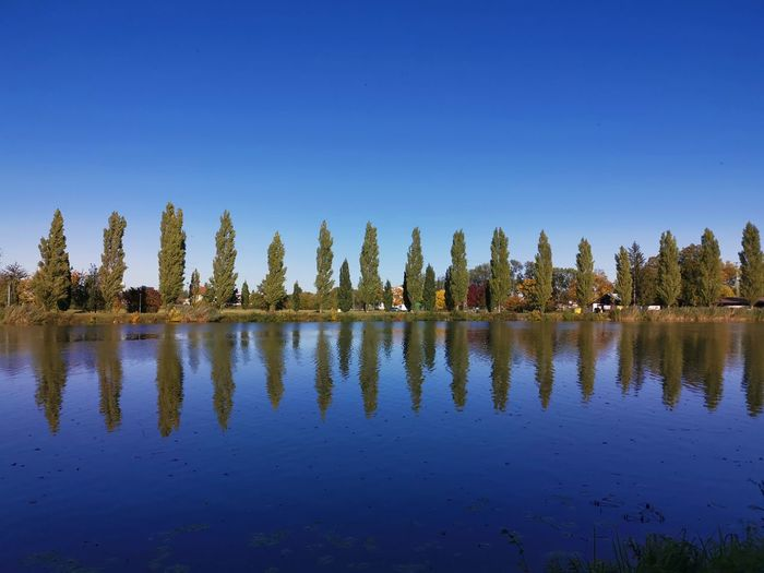 Panoramic view of lake against clear blue sky