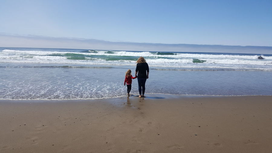 Rear view of woman standing with daughter at beach